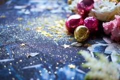 Kerstmisachtergrond met heldere gouden sterren, rode en gele ballen De nieuwjaardenneappels decore met sterren Stock Fotografie