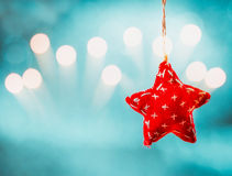Kerstmisachtergrond met het hangen van rode voddenster en vakantie bokeh Royalty-vrije Stock Foto's