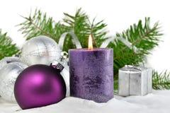 Kerstmisachtergrond met kaars en decoratie Purpere en zilveren Kerstmisballen over sparrentakken in de sneeuw Stock Afbeeldingen