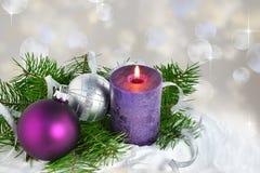 Kerstmisachtergrond met kaars en decoratie Purpere en zilveren Kerstmisballen over sparrentakken in de sneeuw Stock Foto's