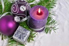Kerstmisachtergrond met kaars en decoratie Purpere en zilveren Kerstmisballen over spartakken in de sneeuw Stock Foto
