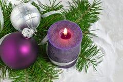 Kerstmisachtergrond met kaars en decoratie Purpere en zilveren Kerstmisballen over spartakken in de sneeuw Stock Afbeeldingen
