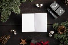 Kerstmisachtergrond met Kerstmisdecoratie, houten kalender en leeg wit notitieboekje Kerstmistak en klokken Royalty-vrije Stock Foto's