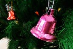 Kerstmisachtergrond met klokken op de Kerstboom Stock Foto