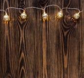 Kerstmisachtergrond met koordlichten uitstekende slinger op houten planken Stock Foto