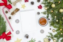 Kerstmisachtergrond met leeg spiraalvormig notitieboekje, spartakken en kegels, Kerstmisdecoratie, giftdozen en theekop stock afbeelding