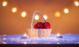 Kerstmisachtergrond met mand met rode appelen, kaarsen, sneeuw en bokeh lichten stock foto's