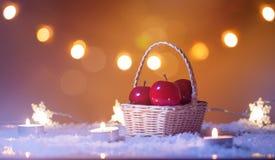 Kerstmisachtergrond met mand rode appelen, kaarsen, sneeuw, sterren en bokeh lichten Stock Fotografie