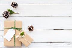 Kerstmisachtergrond met met de hand gemaakte huidige giftdozen en rustieke decoratie op witte houten raad Royalty-vrije Stock Afbeelding