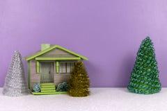 Kerstmisachtergrond met plattelandshuisje en speelgoedbomen stock afbeeldingen