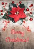 Kerstmisachtergrond met poinsettia, rode snuisterijen en sneeuw op wo Stock Foto's