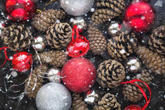 Kerstmisachtergrond met rode zilveren ballen en pinecone Stock Fotografie
