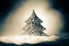 Kerstmisachtergrond met sneeuwspar De sneeuw behandelde helder Kerstboomtribunes uit tegen de donkerblauwe (of groene) tonen o Stock Foto