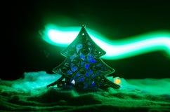 Kerstmisachtergrond met sneeuwspar De sneeuw behandelde helder Kerstboomtribunes uit tegen de donkerblauwe (of groene) tonen o Stock Foto's