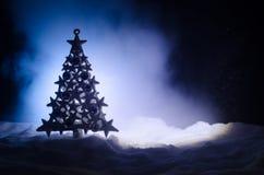 Kerstmisachtergrond met sneeuwspar De sneeuw behandelde helder Kerstboomtribunes uit tegen de donkerblauwe (of groene) tonen o Stock Afbeeldingen