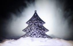 Kerstmisachtergrond met sneeuwspar De sneeuw behandelde helder Kerstboomtribunes uit tegen de donkerblauwe (of groene) tonen o Royalty-vrije Stock Afbeelding
