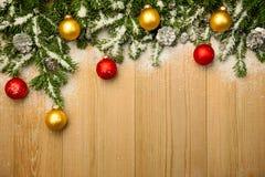 Kerstmisachtergrond met spar en snuisterijen op hout met sneeuw Stock Foto's