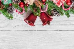 Kerstmisachtergrond met spar, Kerstmisklokken, suikergoed, giftvakjes, bessen en denneappels op witte houten lijst stock foto