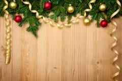 Kerstmisachtergrond met spar, snuisterijen en linten op hout Stock Afbeelding