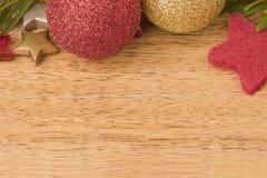 Kerstmisachtergrond met spar, snuisterijen en sterren op hout Stock Afbeelding