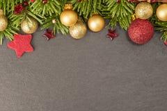Kerstmisachtergrond met spar, snuisterijen en sterren op lei Royalty-vrije Stock Afbeeldingen