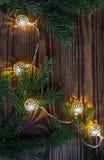 Kerstmisachtergrond met uitstekende slinger en blauwe spartakken koordlichten Royalty-vrije Stock Foto