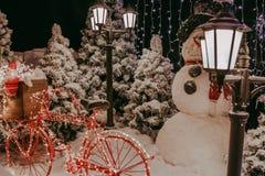 Kerstmisachtergrond, sneeuwman, lichten, rode fiets Stock Foto's