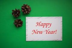 Kerstmisachtergrond van denneappels met Witboekkaart Nieuwjaar en Vrolijk Kerstmisconcept stock afbeeldingen