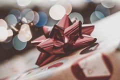 Kerstmisachtergrond van dichte omhooggaand van glanzende rode boog met vage lichten of bokeh op de achtergrond stock afbeelding