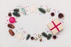 Kerstmisachtergrond van giftvakje, spar, naaldboomkegel en vakantiedecoratie op de witte mening van de lijstbovenkant Vlak leg he Stock Afbeeldingen
