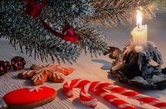 Kerstmisavond, een brandende kaars en een Kerstmispeperkoek, karamelsnoepjes stock afbeeldingen