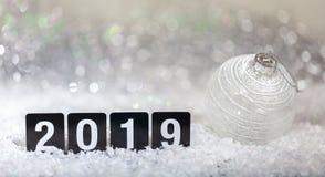 Kerstmisbal en nieuw jaar 2019, op sneeuw, de abstracte achtergrond van bokehlichten stock fotografie