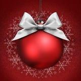 Kerstmisbal met de zilveren boog van het satijnlint op rood Stock Foto