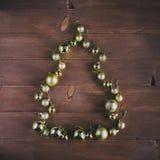 Kerstmisballen in een vorm van Kerstboom op een houten achtergrond Stock Fotografie
