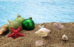 Kerstmisballen en shells op zand Stock Afbeelding