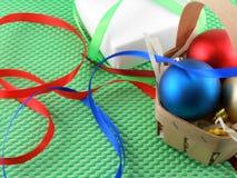 Kerstmisballen en witte giftdoos op groen Royalty-vrije Stock Afbeeldingen