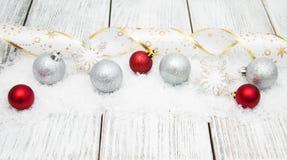 Kerstmisballen met lint op sneeuw Stock Afbeelding