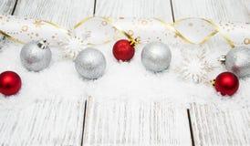 Kerstmisballen met lint op sneeuw Stock Afbeeldingen