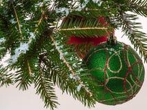 Kerstmisballen op een Kerstboomtak met sneeuw wordt behandeld die Stock Foto