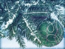 Kerstmisballen op een Kerstboomtak met sneeuw wordt behandeld die wijnoogst Stock Fotografie