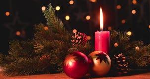 Kerstmisballen op houten lijst met kaars stock video