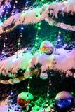 Kerstmisballen op spar onder sneeuw en heldere Kerstmisdeco Royalty-vrije Stock Fotografie