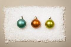 3 Kerstmisballen in rij op sneeuwachtergrond Stock Afbeelding