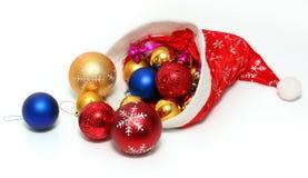 Kerstmisballen, speelgoed in rode hoed van Santa Claus Royalty-vrije Stock Afbeelding