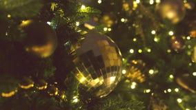 Kerstmisballen van gouden kleur en slingers met bollen op de takken van Kerstmisboom, close-upmening stock footage