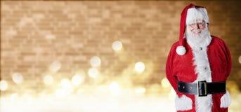 Kerstmisbanner met joviaale Santa Claus die zich voor een bakstenen muur met het fonkelen bokeh van partijlichten en exemplaarrui stock fotografie