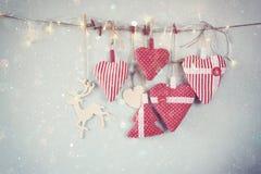 Kerstmisbeeld van stoffen rode harten en boom houten rendier en slingerlichten, die op kabel hangen Royalty-vrije Stock Foto's