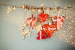 Kerstmisbeeld van stoffen rode harten en boom houten rendier en slingerlichten, die op kabel hangen Stock Afbeeldingen