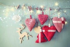 Kerstmisbeeld van stoffen rode harten en boom houten rendier en slingerlichten, die op kabel hangen Stock Foto