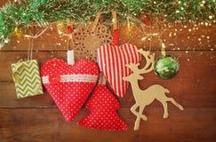 Kerstmisbeeld van stoffen rode harten en boom houten rendier en slingerlichten, die op kabel voor houten achtergrond hangen Stock Foto's